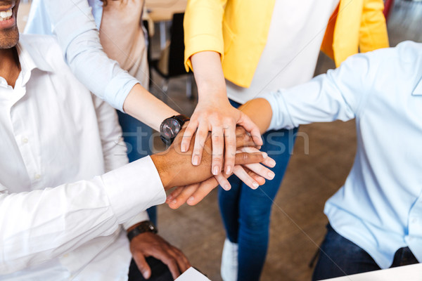 Multiethnic group of young people standing and joining hands Stock photo © deandrobot