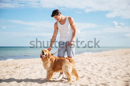 Man with dog standing and looking far away on beach Stock photo © deandrobot