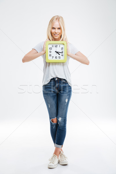 Full length of happy young woman standing and holding clock Stock photo © deandrobot