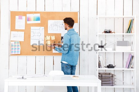 Back view of a businessman posting task stickers on board Stock photo © deandrobot