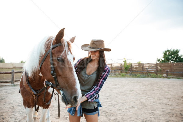 Cheerful woman cowgirl standing and taking care of her horse Stock photo © deandrobot