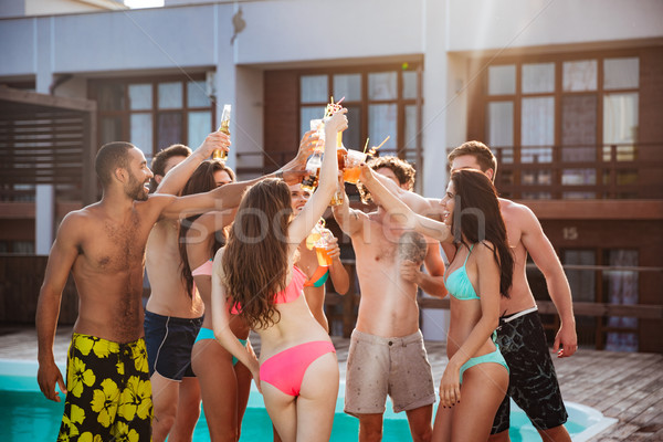 Group of best friends having fun dancing at swimming pool Stock photo © deandrobot