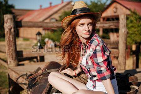 Cute redhead cowgirl sitting and resting on the ranch fence Stock photo © deandrobot