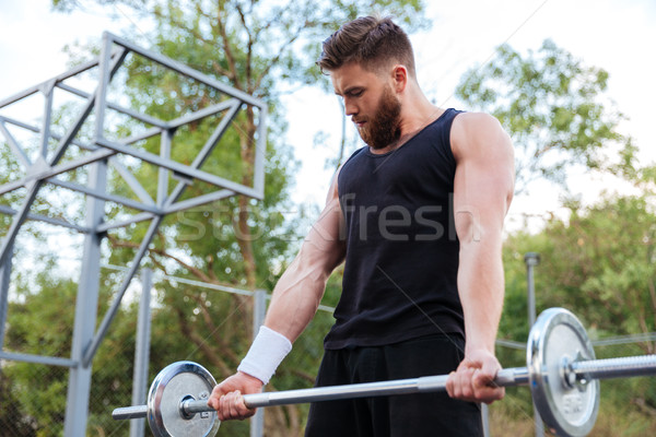 Serious young bearded fitness man lifting barbell Stock photo © deandrobot