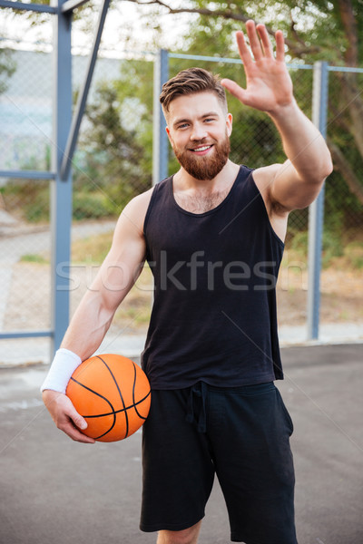 Young smiling bearded basketball player greeting somebody with hand waving Stock photo © deandrobot