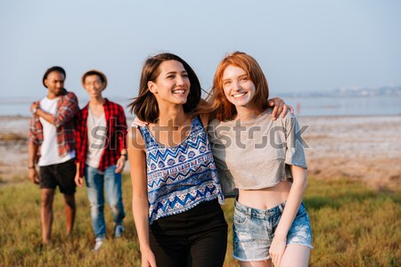 Two cheerful girls laughing while their boyfriends talking outdoors Stock photo © deandrobot