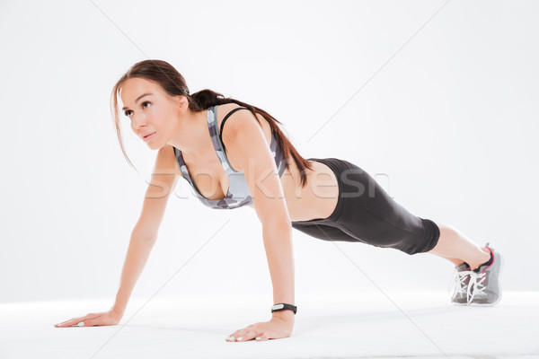 Young fitness woman shakes press Stock photo © deandrobot