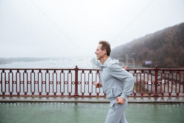 Side view of Man running on bridge Stock photo © deandrobot