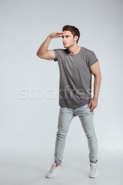 Full length portrait of a man straring far away Stock photo © deandrobot
