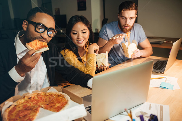 Happy colleagues working at night with laptops while eating pizz Stock photo © deandrobot