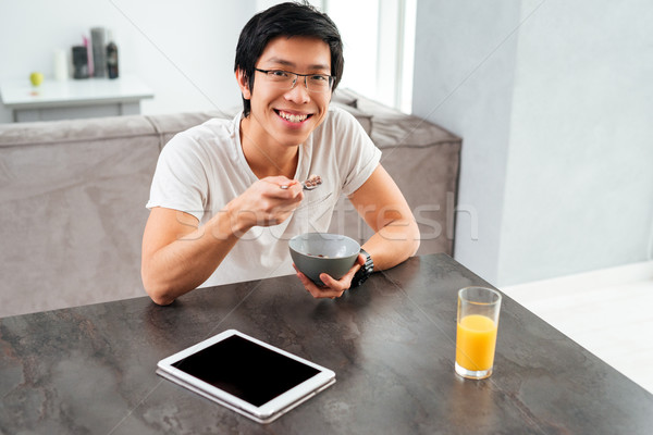 Young asian man with cereal Stock photo © deandrobot