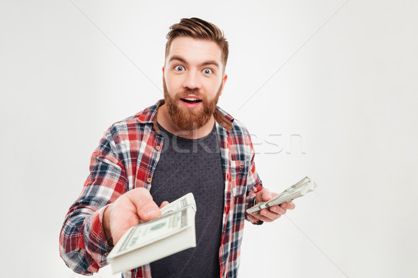 Casual bearded man in plaid shirt giving money to camera Stock photo © deandrobot