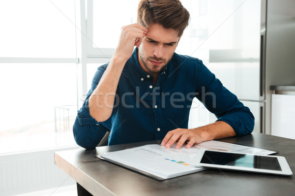 Concentrated young man analyzing his finances at home Stock photo © deandrobot