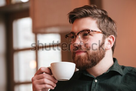 Happy bearded young man drinking coffee. Stock photo © deandrobot