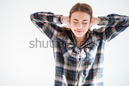 Pretty young woman in plaid shirt with hands on head Stock photo © deandrobot