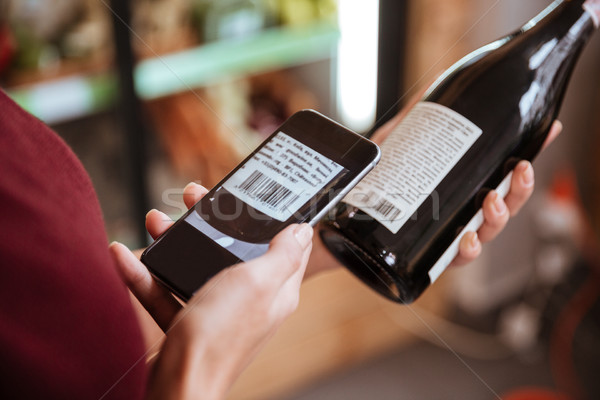 Woman scanning bar code with mobile phone on wine bottle Stock photo © deandrobot