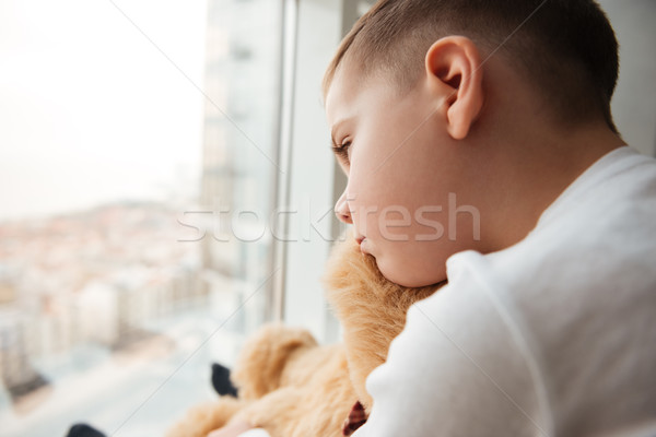 Alone little sad boy with teddy bear near window Stock photo © deandrobot