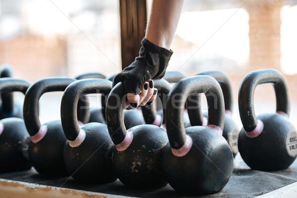Sportswoman taking kettlebell in gym Stock photo © deandrobot
