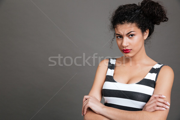 Irritated african american young woman standing with arms crossed Stock photo © deandrobot