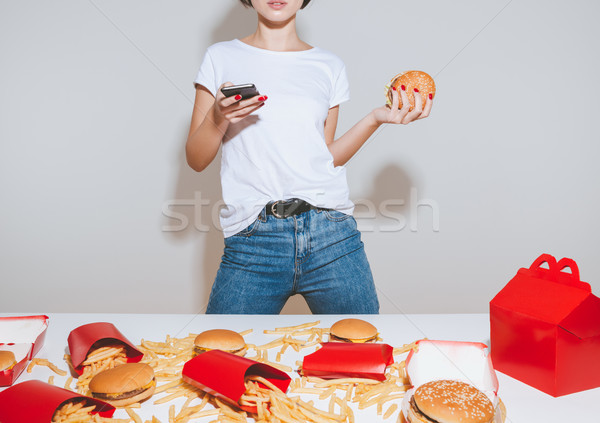 Closeup of young woman with burger standing and using smartphone Stock photo © deandrobot