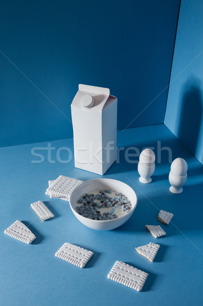 Pack of milk, eggs, cookies and chocolate balls in bowl Stock photo © deandrobot