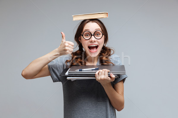 Happy Female nerd with book on head Stock photo © deandrobot