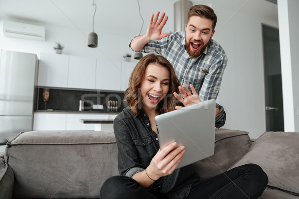 Loving couple in kitchen waving to friends by tablet computer Stock photo © deandrobot