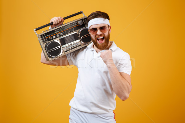 Happy young man wearing sunglasses holding tape recorder Stock photo © deandrobot