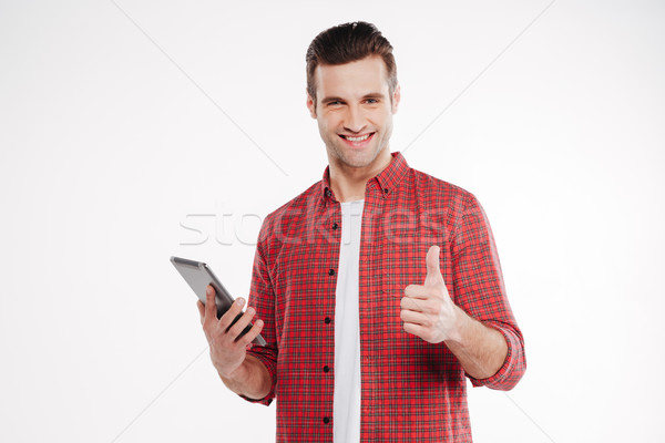 Smiling man holding tablet computer and showing thumb up Stock photo © deandrobot