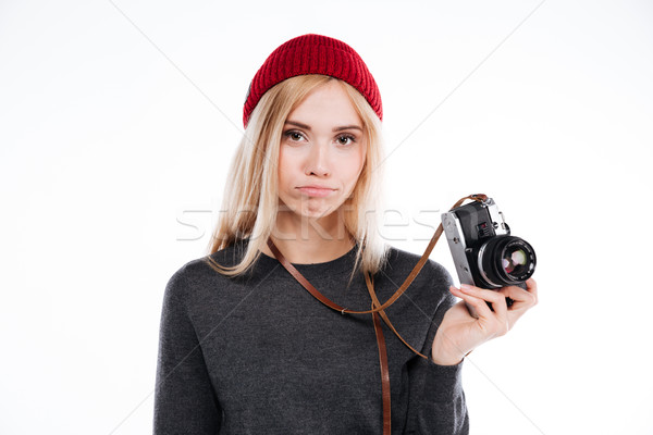 Sad upset girl in hat standing and holding retro camera Stock photo © deandrobot
