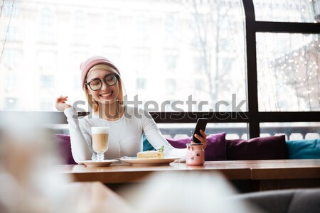 Happy young woman listening to music and eating in cafe Stock photo © deandrobot