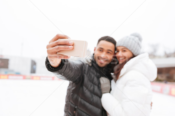 Cheerful couple skating at ice rink make selfie by phone. Stock photo © deandrobot