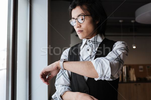 Handsome young asian man looking at watch. Stock photo © deandrobot