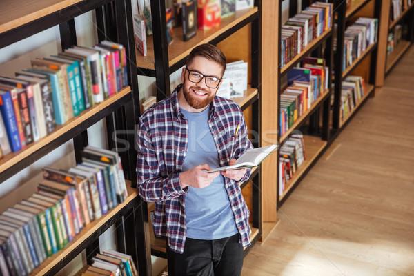 Foto stock: Feliz · barbado · joven · pie · lectura · biblioteca