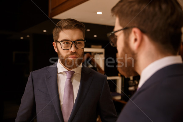 Serious young bearded businessman looking at mirror. Stock photo © deandrobot
