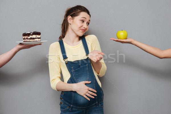 Jonge verward zwangere vrouw kiezen appel room Stockfoto © deandrobot