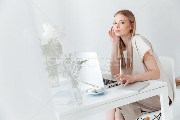 Grave mujer sesión usando la computadora portátil foto Foto stock © deandrobot