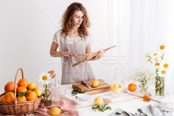 Woman standing indoors near table with a lot of citruses Stock photo © deandrobot