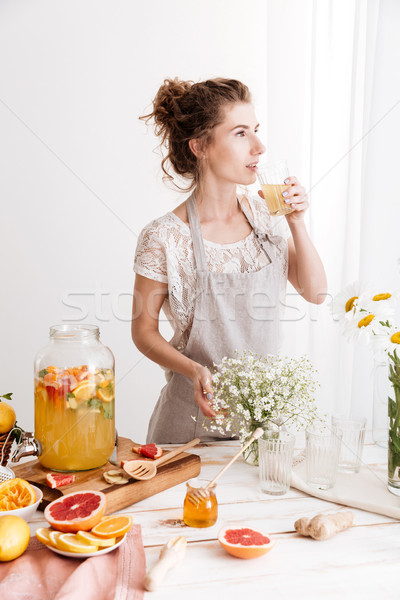 Woman standing indoors drinking citrus beverage Stock photo © deandrobot