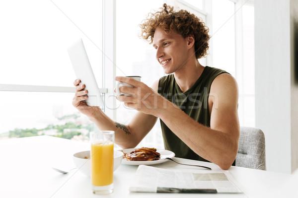 Stock fotó: Jóképű · boldog · férfi · táblagép · iszik · kávé