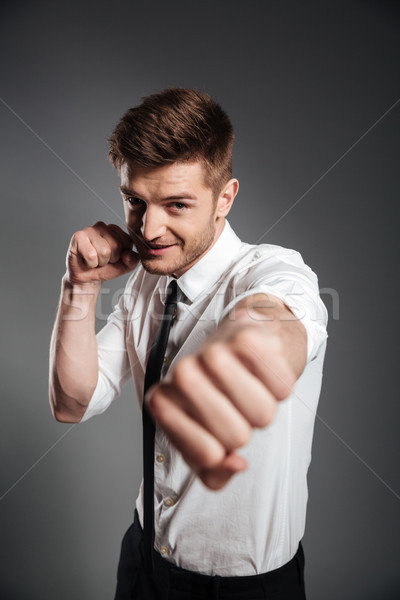 Handsome young businessman in formalwear boxing Stock photo © deandrobot