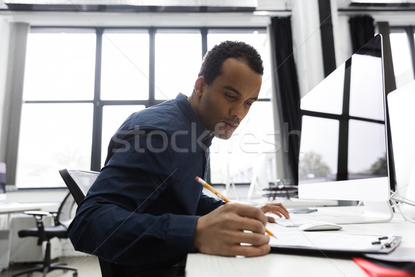 Afro american businessman making notes while sitting at his desk Stock photo © deandrobot