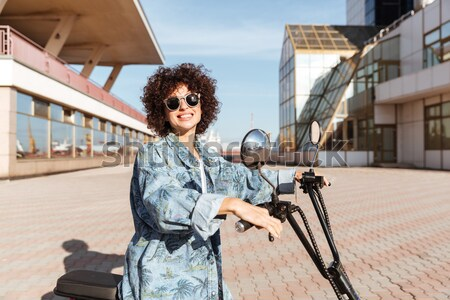 Image of happy curly woman in sunglasses sitting on motorbike Stock photo © deandrobot