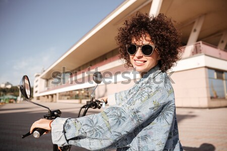 Side view of smiling girl in sunglasses posing on motorbike Stock photo © deandrobot