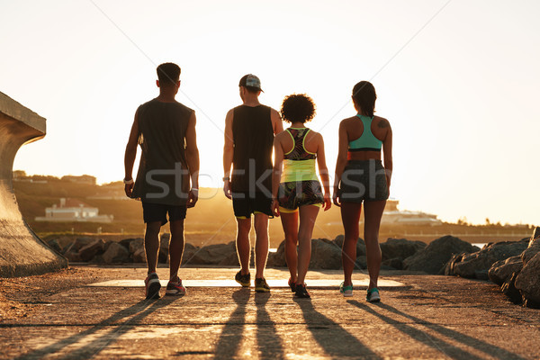 Full length back view image of fitness people walking outdoors Stock photo © deandrobot