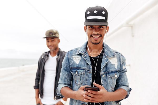 Young african men friends walking outdoors listening music. Stock photo © deandrobot