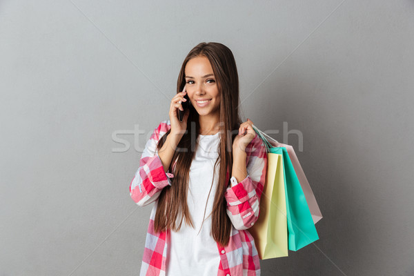 Stock photo: Portrait of smiling young woman holding shopping bags talking on