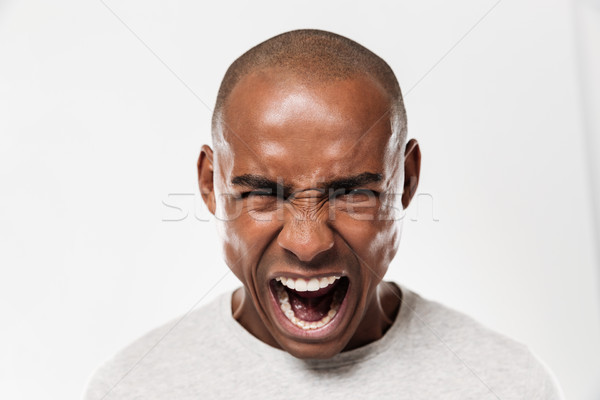 Emotional screaming young african man Stock photo © deandrobot