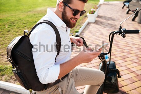 Side view of Cool bearded man in sunglasses with backpack Stock photo © deandrobot