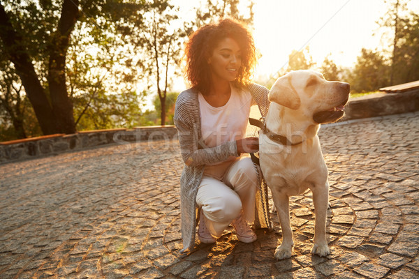 Young smiling lady in casual clothes sitting and hugging dog in park Stock photo © deandrobot